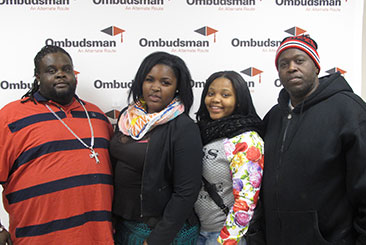 Image is of four people, two women and two men standing in front of a wall print of the Ombudsman logo.