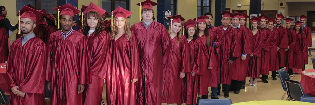 Image is of a group of students in their graduation caps and gowns.