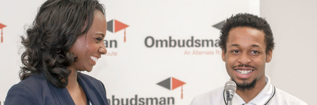 Image is of an adult woman and a male student at a microphone in front of the Ombudsman logo.