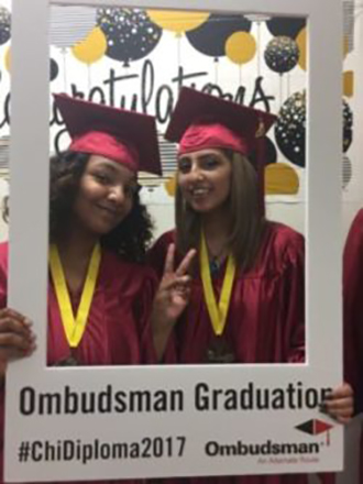 "Image is of two female students in their cap and gown at graduation holding up a paper frame that says ""Ombudsman Graduation #ChiDiploma2017""."