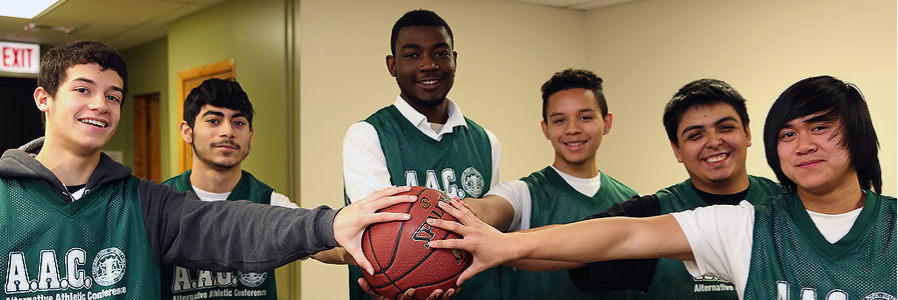 Image is of six male students wearing green jerseys. They have all extended their hands to grasp a basketball.
