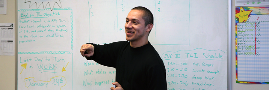 Image is of one student standing, smiling, and pointing to his right. Student is wearing a black shirt and standing in front of a white dry erase board with green writing on it.