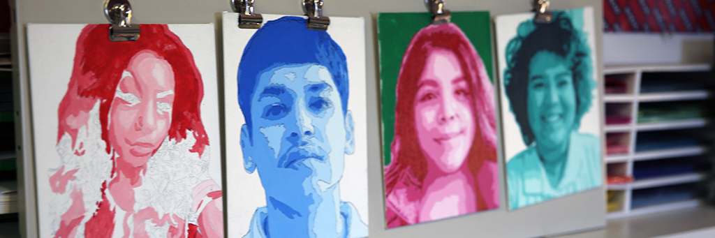 Image is of artistic renderings of four student portraits. From left to right: female student's face and features are shades of pink and purple with a white background, male student's features are shades of blue with a white background, female student's features are shades of pink with a green background, and female student's features are shades of blue with a white background.