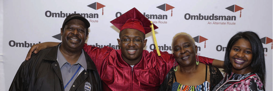 Image is of student in his graduation cap and gown with his arms around his family to his sides.