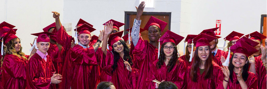 Image is of a large group of students standing and celebrating in their graduation caps and gowns.