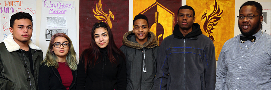 Image is of five students to the right side of one male teacher. Behind them is a maroon and yellow poster with a Trojan helmet and two phoenixes.