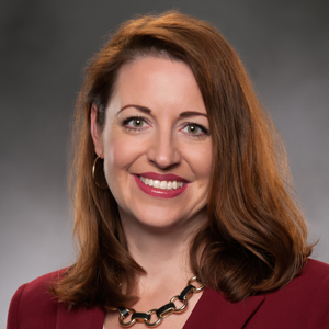 Image of Allison O'Neil, President and COO, in red blazer.