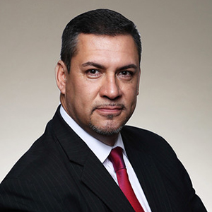 Image of Rudolph Flores, Senior Vice President, Operations, in black suit coat and red tie.