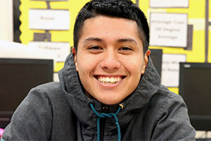 Image is of student smiling in gray hoodie in the foreground with 4 computer monitors behind him. Classroom wall behind monitors has a yellow bulletin board with white and black paper depicting a flow chart or diagram.