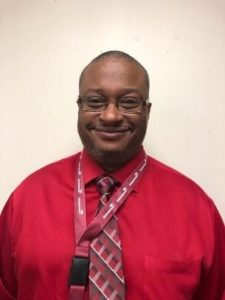 headshot-style photo of Principal Robert Turner. Robert is wearing a bright red shirt and a purple tie and smiles at the camera